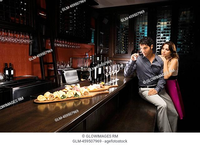 Young man drinking wine at a bar counter with a mid adult woman standing beside him