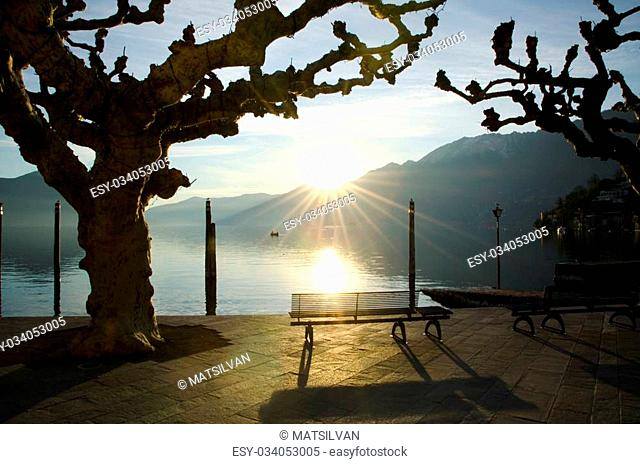 Bench on the lakefront in an alpine lake with mountains and sunset
