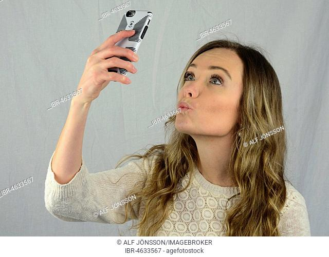 Young woman make a selfie with a mobil phone, kissing lips