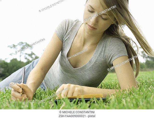Woman lying in grass, writing