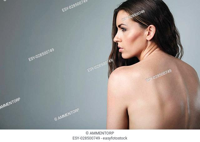 Naked woman looking away at copy space on grey background. Topless caucasian female model