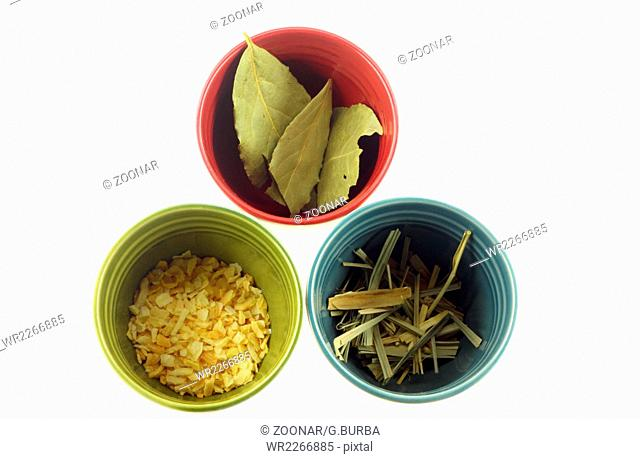 Colorful cups with herbs and spices on white background
