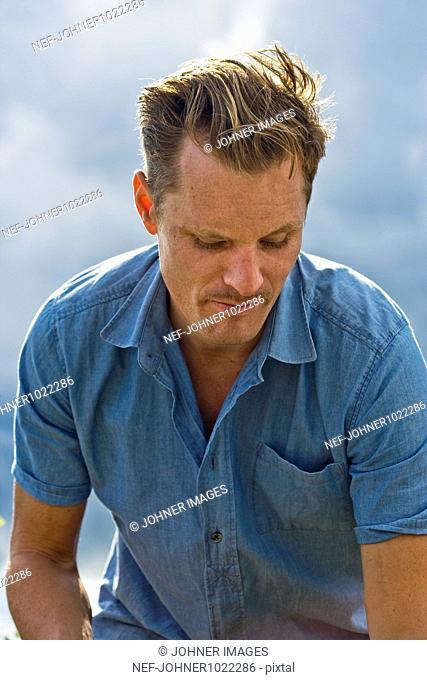 Scandinavia, Sweden, outdoor portrait of mid adult man looking down