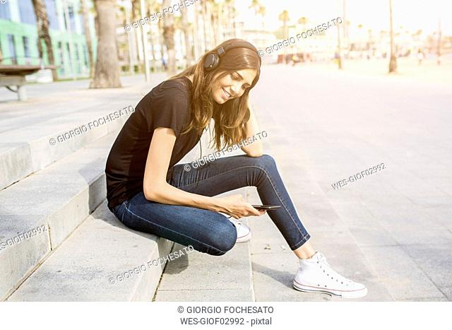 Smiling young woman sitting on steps listening to music