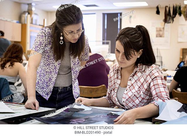Art teacher reviewing student's artwork
