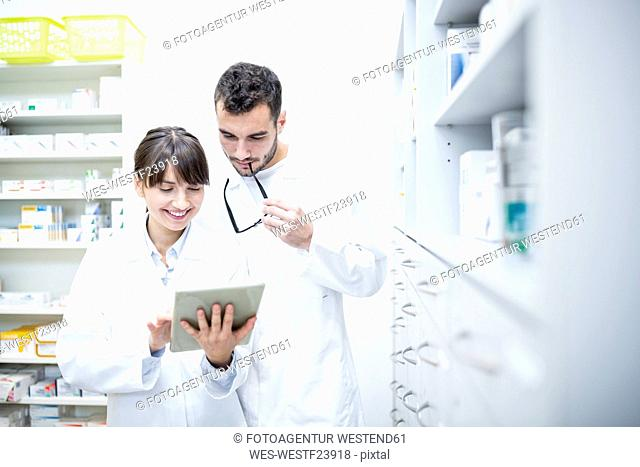 Two pharmacists using tablet in pharmacy