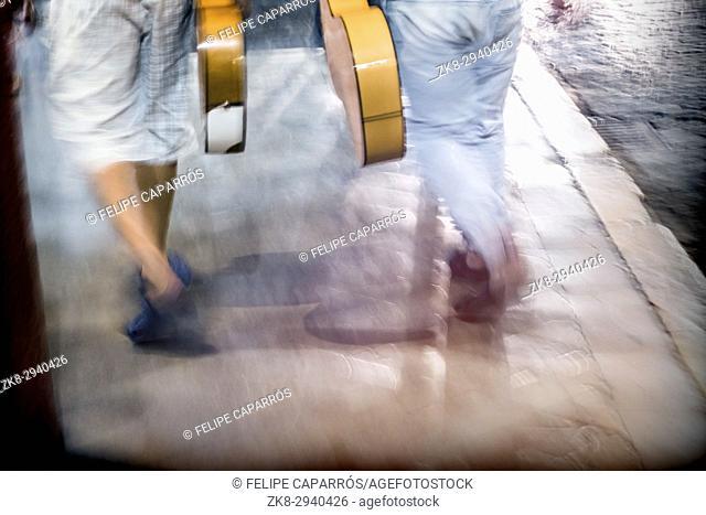 Unrecognizable pedestrian walking with guitars, selective blur, travel concept