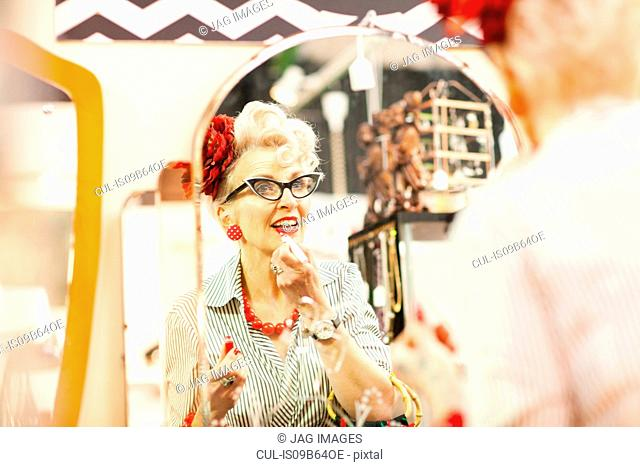 Mirror image of quirky vintage woman applying lipstick in antique and vintage emporium