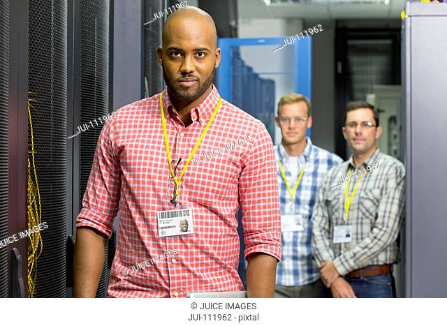Team of technicians looking at camera in server data centre
