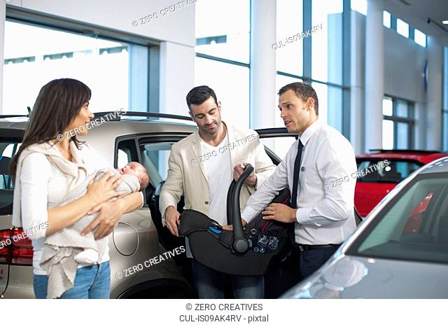 Salesman chatting to mid adult couple with baby girl in car dealership