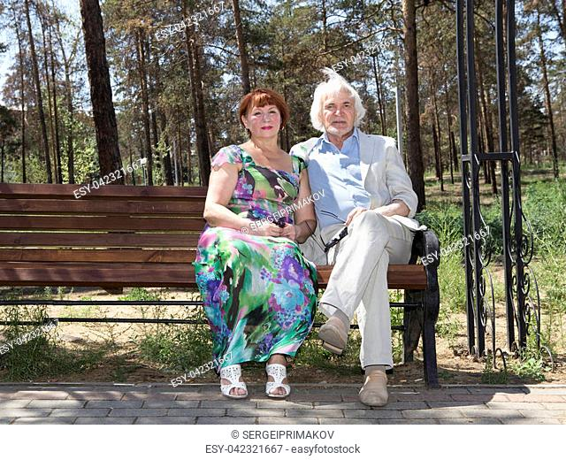 Mature husband and wife sitting on a wooden bench in a recreation park
