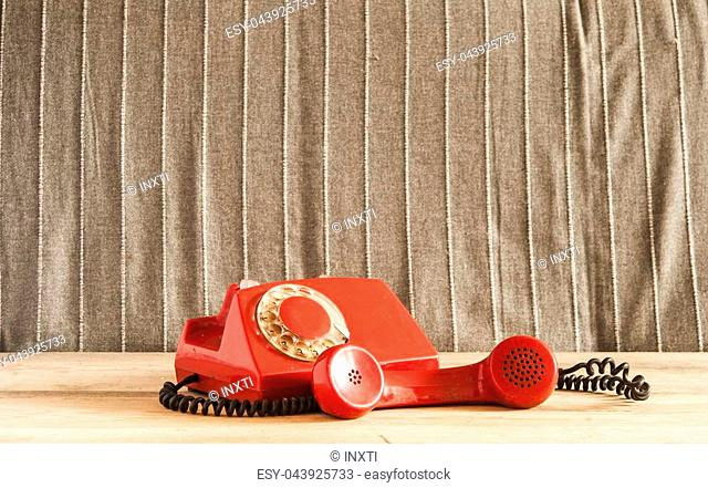 Dirty red vintage phone on pine wooden table