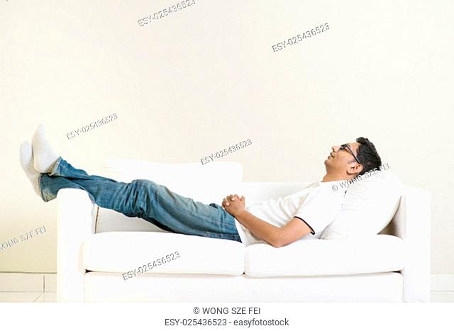 Indian guy daydreaming and rest at home. Asian man relaxed and sleep on sofa indoor. Handsome male model