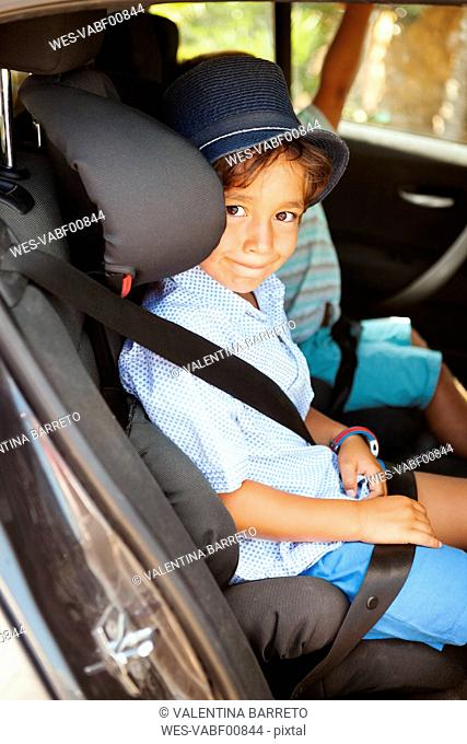 Portrait of smiling little boy sitting on backseat of a car