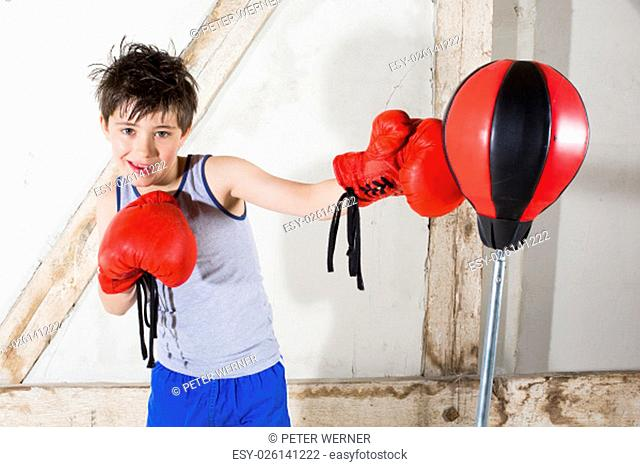 young boy with red boxing gloves