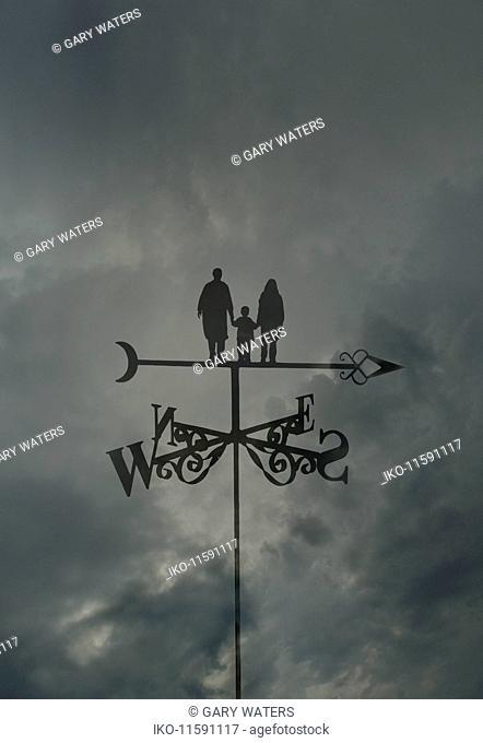 Family standing on top of arrow on weather vane against gloomy sky