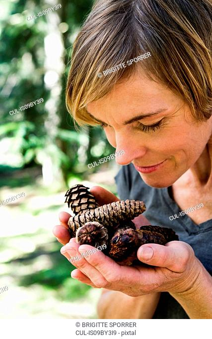 Woman with handful of pine cones in forest