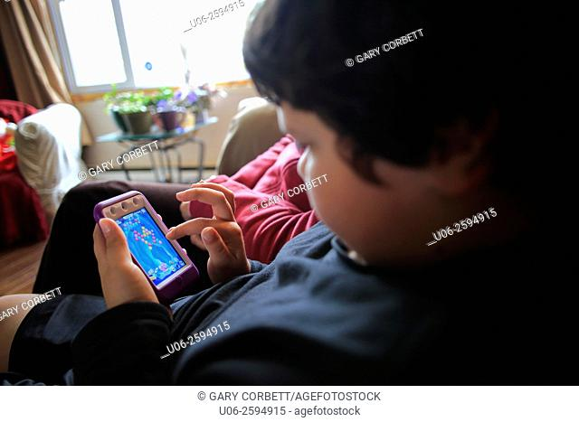 A boy playing a game on an ipod