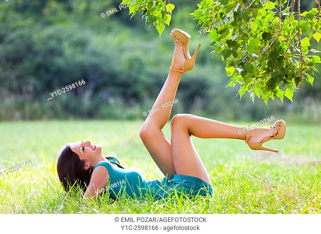 Playful young woman in nature reaching tree-branches