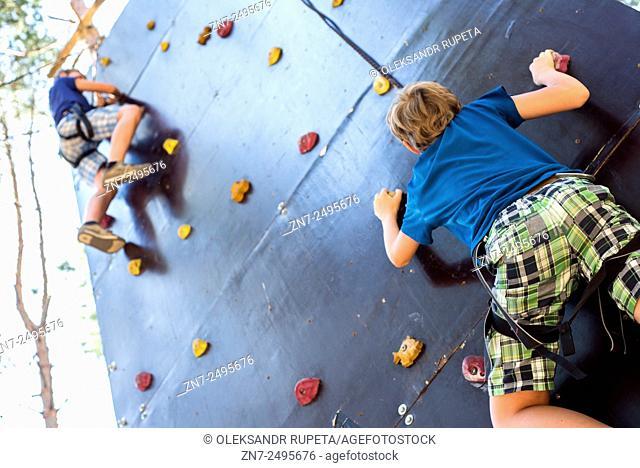Scouts training on artificial outdoor climbing wall in Ukrainian scout training camp, Kiev region, Ukraine