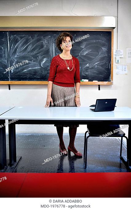 A teacher in a classroom, standing behind a Chair. Behind a chalkboard. Rome (Italy), May 2014