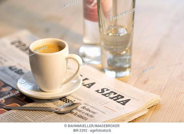 Italian cafe espresso coffee with newspaper and Grappa