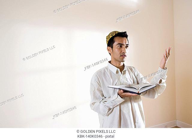 A Muslim man holding Koran