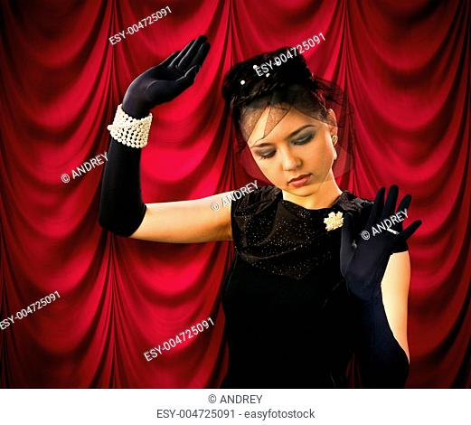 Theatrical actress on the background of red drapes