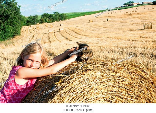 Girl with cat on hay bale in field
