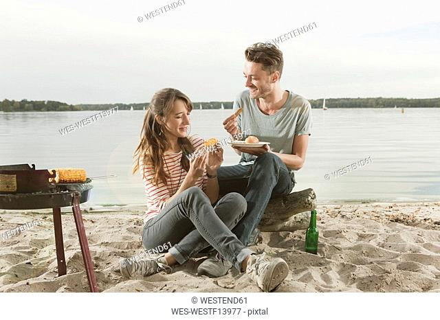 Germany, Berlin, Lake Wannsee, Young couple having corn and sausage