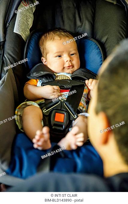 Caucasian father admiring baby boy in car seat
