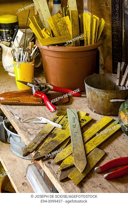 Plant labels and hand tools on the work bench in a garden shed