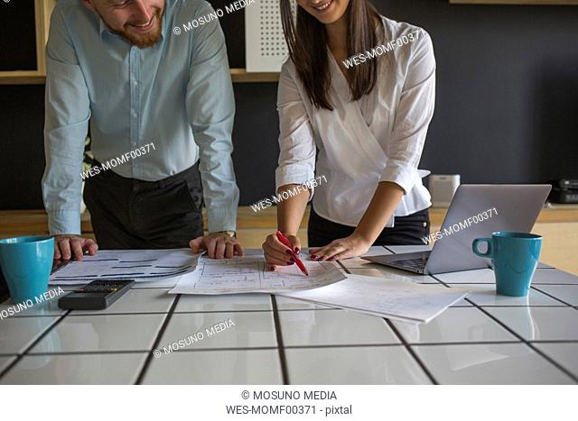 Smiling man and woman studying plans on table at home