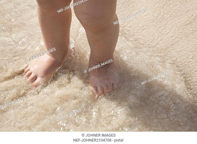 Child standing on beach, low section