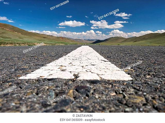 Wide-angle shot of empty road markings on asphalt in Mongolia between mongolian towns Tsagaannuur and Bayan-Olgii under blue sky