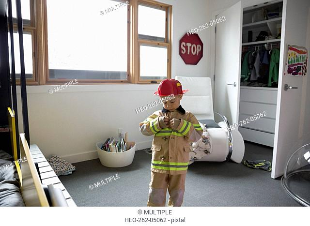 Boy putting on fireman costume in bedroom