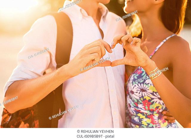 Cropped shot of young couple making hand heart shape together, Koh Samui, Thailand