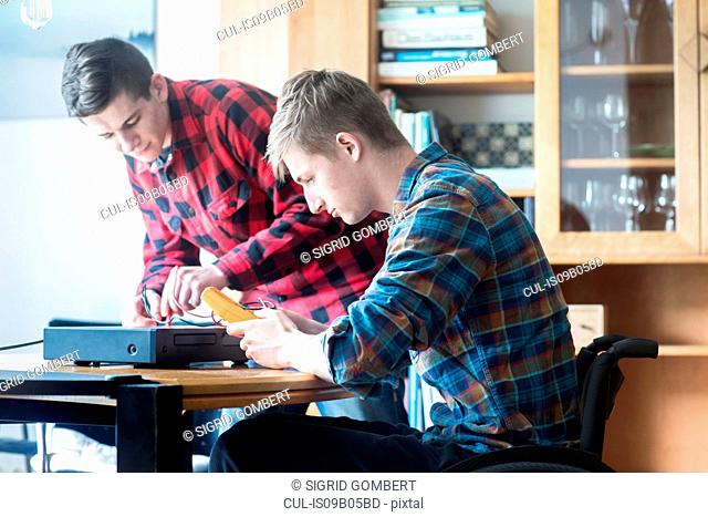 Young man using wheelchair connecting control panel and transformer with friend at kitchen table