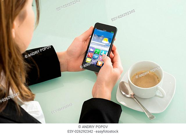 Close Up Of Businesswoman Checking Weather Forecast On Smartphone In Office