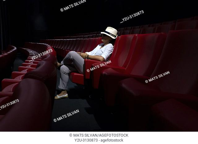 Woman with Hat Sitting Alone in Movie Theater