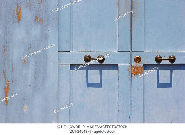 Peeling blue painted doors with pair of metal handles, Burano, Venetian, Lagoon, Veneto, Italy, Europe