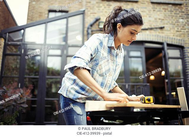 Young woman measuring wood on patio