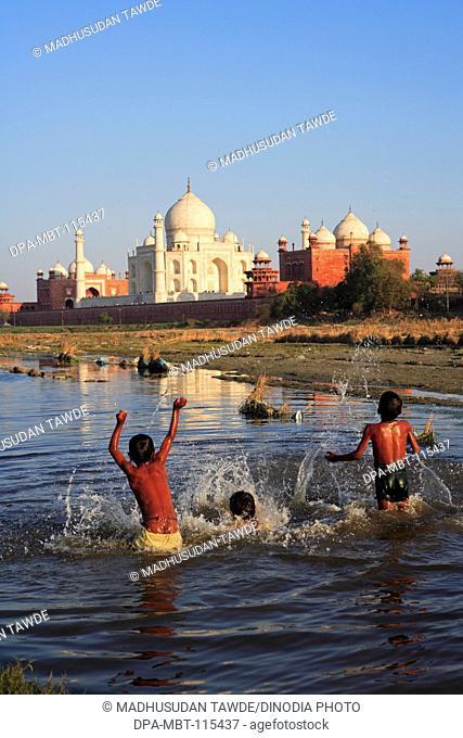 Children playing in Yamuna river at Taj Mahal Seventh Wonders of World , Agra , Uttar Pradesh , India UNESCO World Heritage Site