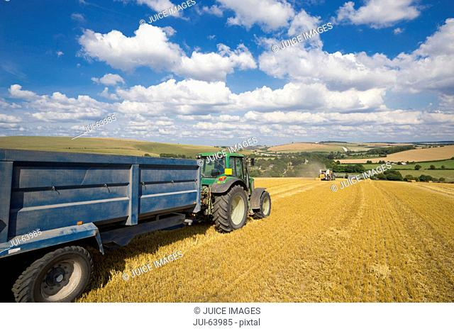 Tractor pulling trailer, with straw bales in sunny rural field