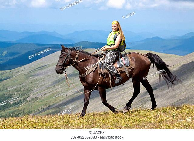 Female rider with backpack on horseback at mountains