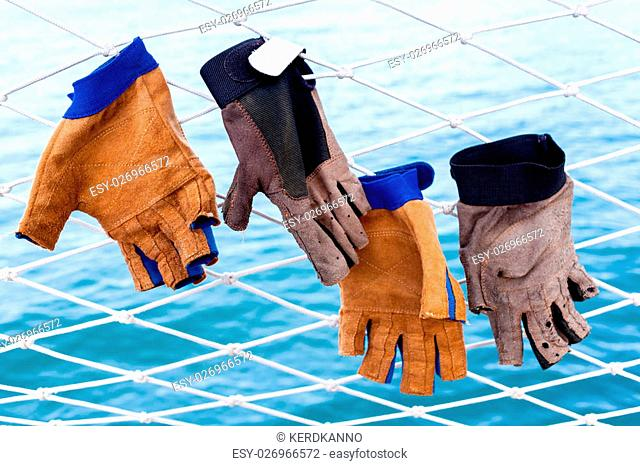 Sailing glove hanging on the nets of sailing yacht