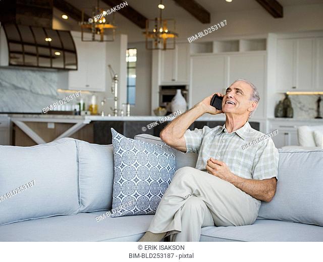Caucasian man sitting on sofa talking on cell phone