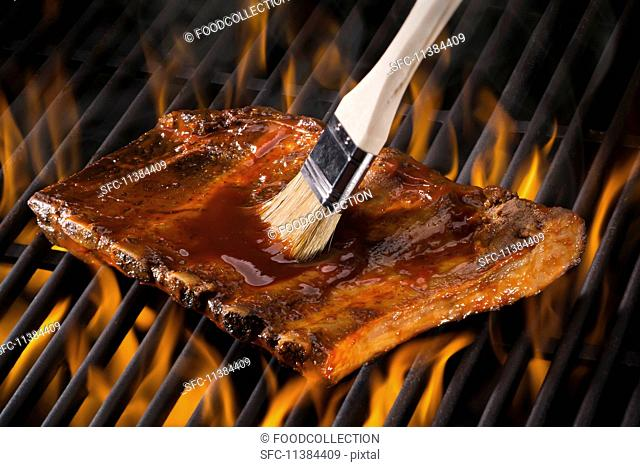 Spare ribs being brushed with marinade on a hot grill