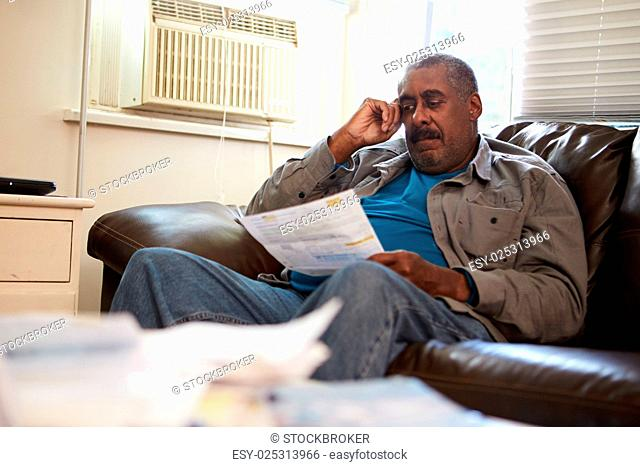 Worried Senior Man Sitting On Sofa Looking At Bills