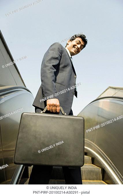 Businessman standing on an escalator, Gurgaon, Haryana, India